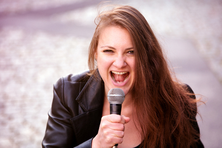 portrait of young brunette woman singing with microphone outdoors