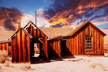 old wooden abandoned house in the desert at sunset Stock Photo