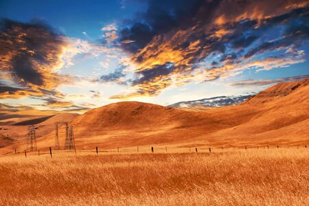 colorful view of dry farmland at sunset