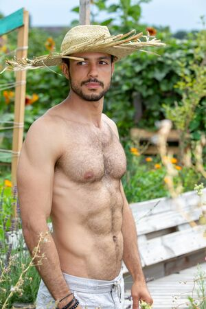 handsome hairy shirtless man with straw hat standing in garden