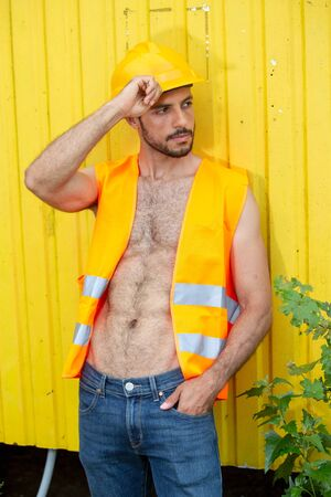 portrait of shirtless worker with yellow construction helmet