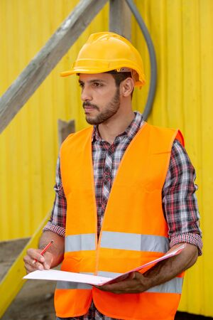 construction worker with yellow helmet and orange vest holding a folder and pen