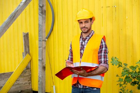 Construction worker with yellow helmet and orange vest holding a folder