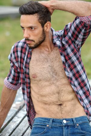 portrait of sexy bearded man with open shirt sitting outdoors