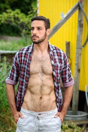 portrait of handsome bearded man standing outdoors with open shirt