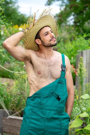 handsome sexy gardener with green pants and straw hat standing in garden Stok Fotoğraf