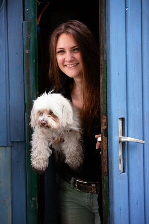 portrait of young brunette woman holding her dog and standing at blue door