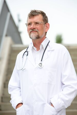 portrait of handsome doctor in his 50s standing outside Stockfoto