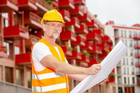 portrait of handsome worker in his 50s with helmet standing outside and holding a plan