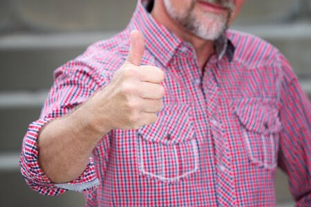 portrait of handsome man in his 50s showing his thumbs up