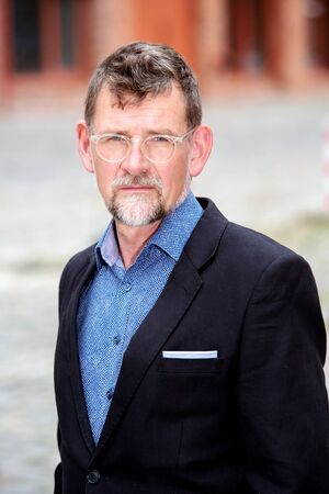 portrait of handsome businessman in his 50s with eyeglasses standing outside