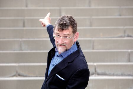 portrait of handsome businessman pointing his finger up to stairs