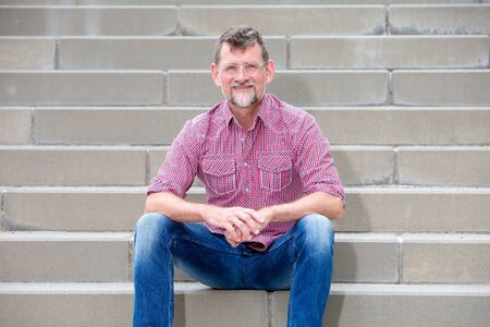 portrait of handsome man in his 50s sitting on steps and smiling