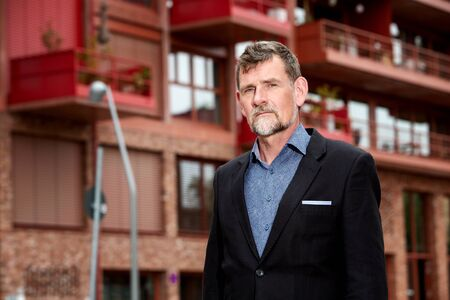 portrait of handsome businessman in his 50s standing in front of building