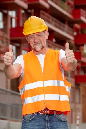 portarit of handsome worker with helmet in his 50s holding thumbs up Stockfoto