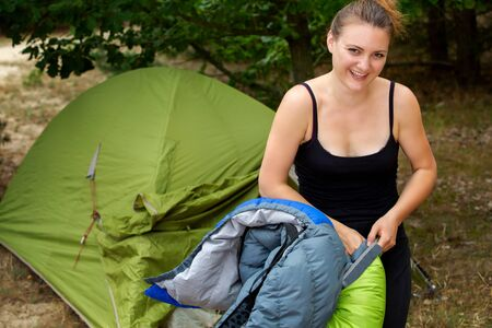 portrait of young woman in front of tent unpacking her sleeping bag