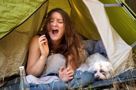 portrait of young woman lying in tent with her white dog and yawning