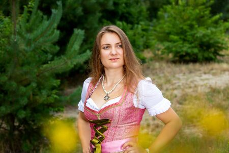 Portrait of young woman in dirndl standing in forest