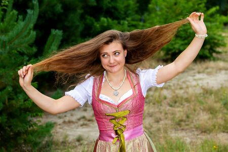 portrait of young woman in dirndl playing with her hair and making grimace Stockfoto