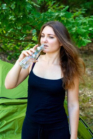 poratrit of young brunette woman standing at her tent and drinking water Stockfoto
