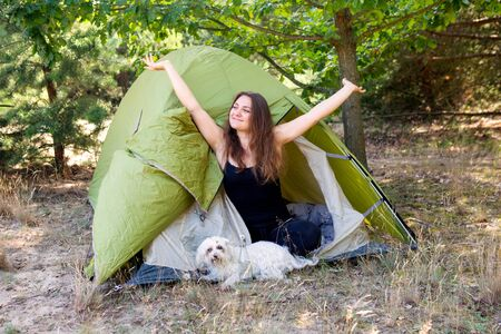 portrait of young woman sitting in front of her tent and spreading her arms
