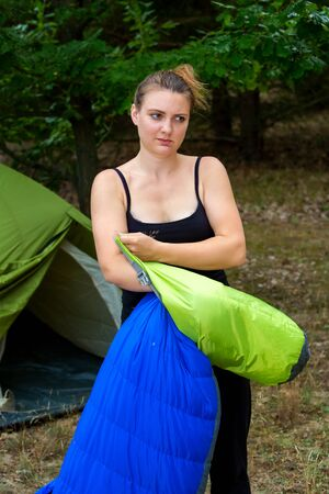 portrait of young woman in front of tent packing her sleeping bag Stockfoto