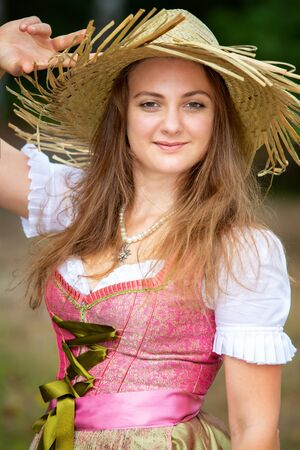 portrait of young woman in dirndl and straw hat standing outdoors Stockfoto