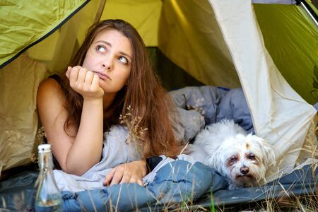 portrait of young woman lying in tent with her white dog