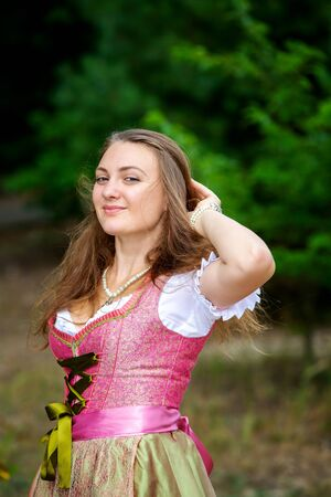 portrait of young woman in dirndl standing in forest and smiles