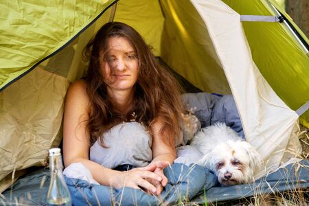 portrait of young woman lying in tent with her white dog and looking tired