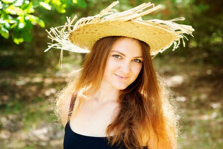 portrait of beautiful young brunette woman with straw hat standing outdoors Stockfoto