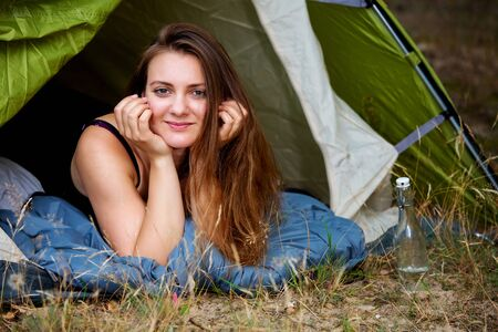 portrait of young brunette woman lying in tent and looking outside