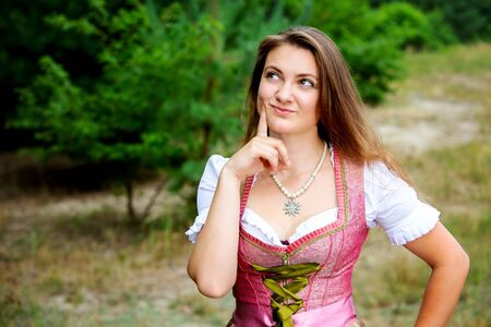 portrait of young woman in dirndl standing outdoors and looking thoughtfull Stockfoto