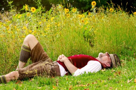 handsome bavarian man lying at field of sunflowers and sleeping Imagens - 130064050