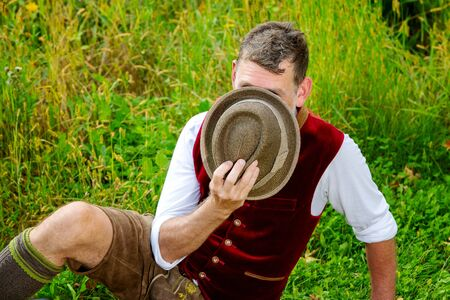 portrait of bavarian man sitting on grass and hiding behind his hat Stockfoto