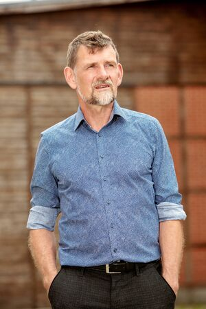 portrait of handsome man in his 50s in blue shirt standing outside Stockfoto