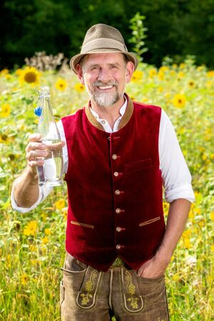 handsome bavarian man standing in field of sunflowers and holding a bottle of water Stockfoto