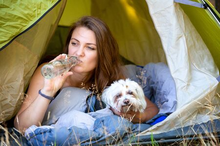 portrait of young woman lying in tent with her dog and drinking water