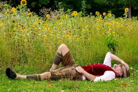 handsome bavarian man lying at field of sunflowers and sleeping