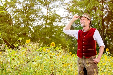 portrait of handsome bavarian man in his 50s standing in a field of sunflowers