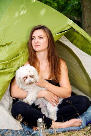 portrait of young woman sitting in front of her tent with her dog