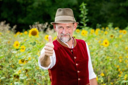 portrait of handsome bavarian man in his 50s standing in garden with thumbs up