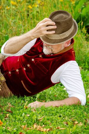 handsome bavarian man lying at field of sunflowers and resting