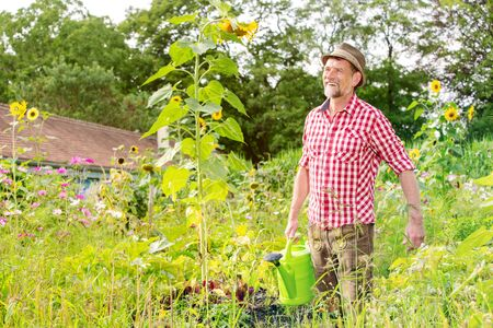 portrait of handsome bavarian man standing in the garden and watering the flowers