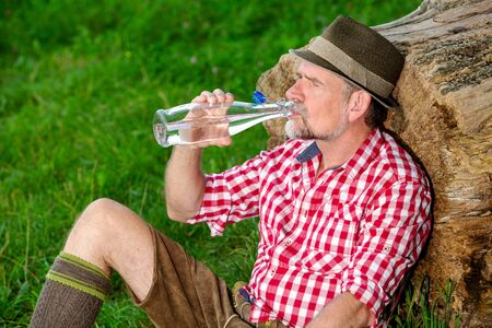 portrait of handsome bavarian man sitting outdoors at tree stump and drinking water