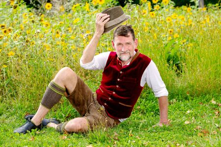 portrait of handsome bavarian man sitting in front of field of sunflowers