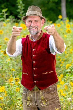 portrait of handsome bavarian man in his 50s standing in garden with thumbs up Stockfoto