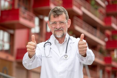 portrait of handsome doctor in his 50s standing outside with his thumbs up