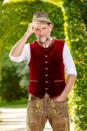 portrait of handsome bavarian man in his 50s standing outdoors in park Stockfoto