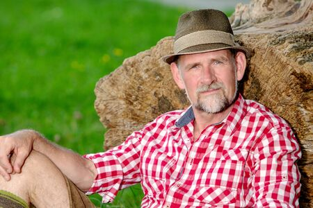 portrait of handsome bavarian man sitting outdoors at tree stump and smiles